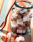 Brown and white sugar lumps in jar