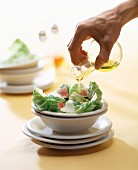 Hand pouring oil over salad