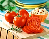 Whole and sliced tomatoes on chopping board