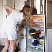 Junge Frau vor offenem Kühlschrank