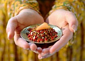 hands holding bowl of spices