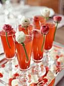 Gläser mit Himbeer-Champagner und Blumendeko