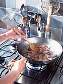 Frau brät Schweinefleisch in einer Pfanne