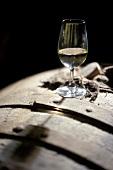 Ein Glas Weisswein auf einem Weinfass