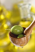 green olives in wooden spoon