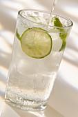 Ein Glas Sprudelwasser mit Eiswürfeln und Limette