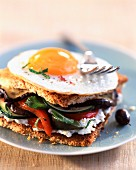 Toasted sandwich with fried egg, vegetables and goat's cheese
