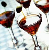 Gläser mit rotem Martini und Oliven-Spiesschen
