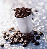 Schoko-Kaffeebohnen mit Becher und Löffel