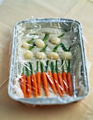 Baby vegetables covered in cling film