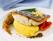Piece of grilled bass with mashed potatoes and courgette flower