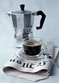 Glastasse mit Kaffee auf Zeitung, Kaffeekocher im Hintergrund
