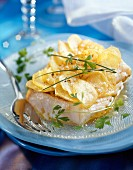 Piece of cod covered with thin slices of potatoes