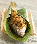 Sea bream in banana leaf with onions and green pepper