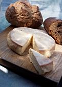 Angeschnittener Abbaye de Cîteaux (französischer Weichkäse) auf Holzbrett mit Brot