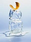 Ein Stück Orangenschale auf zwei Eiswürfeln