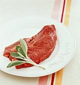 Eine Scheibe Rindfleisch mit Salbei auf einem Teller