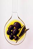 Schwarze Oliven auf Löffel in Olivenöl