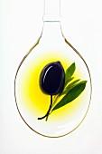 Schwarze Olive auf Löffel in Olivenöl