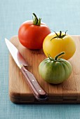 Three different coloured tomatoes on a chopping board