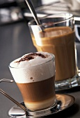 Cappuccino und Kaffee mit Milch in Gläsern
