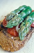 Grilled bread with green asparagus, tomatoes, onions and olive oil