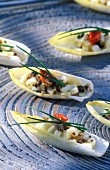 Chicory boats with scallops, green apple and chives on a blue surface