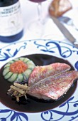Provençal-style red mullet fillet in a red wine sauce on a white plate with an ornamental pattern