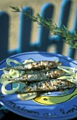 Provençal-style grilled sardines on a blue plate