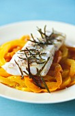 Cod fillet with bay leaves on a yellow pepper medley