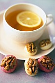 A cup of tea served with marzipan sweets with caramelised walnuts