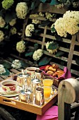 A breakfast tray on a wooden bench with white flowers