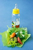 Baby bottle and fresh vegetables