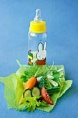 Gemüsestückchen auf Papier und Babyflasche