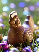 Henne aus Schokolade zu Ostern mit bunten Schokoeiern im Garten