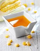 Maiskeimöl in einem Porzellanschälchen mit Maiskörnern