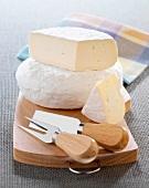 Zwei Laib Tomme auf einem Holzbrett mit Käsebesteck