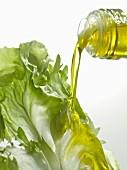 Olivenöl auf ein Salatblatt gießen