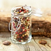 Small glass jar of mixed peppercorns and berries