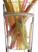 Different coloured straws in a glass of lemonade