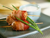 Sausages wrapped in bacon on sticks
