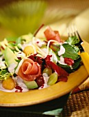 A mixed leaf salad with raw ham and fresh fruits