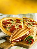 A toasted sandwich, rolled pita bread and a chorizo pizza