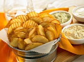 Bucket full of assorted fried potatoes with a selection of dips
