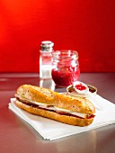 A baguette sandwich with turkey ham, Gruyere cheese and tomato chutney