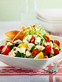 Greek salad with feta cheese and red and yellow tomatoes