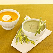 Green cream of asparagus soup, and cream of sweet potato soup with pink pepper