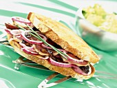 A sandwich from south-west France with smoked duck breast, dried plums and red onions