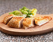 Sliced chicken breast on a chopping board