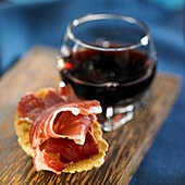 Iberian ham slices and glass of red wine
